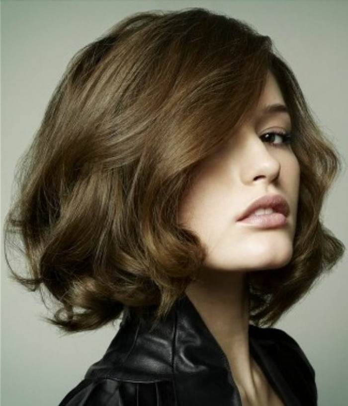 side-swept curled bob, in medium brown hair color, worn by woman in black leather top, with pale nude pink lipstick