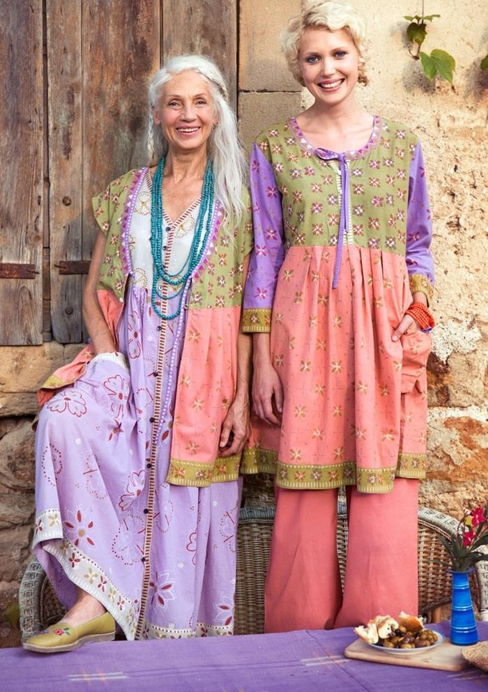 older woman with long white hair, standing next to young blonde woman, both wearing bohemian style outfits, in pale purple, pink and pastel green, with floral pattern and pockets