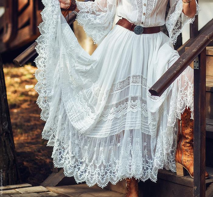 tiered white boho style dress, with lace and frills, worn with vintage brown leather belt, by woman standing on wooden stairs