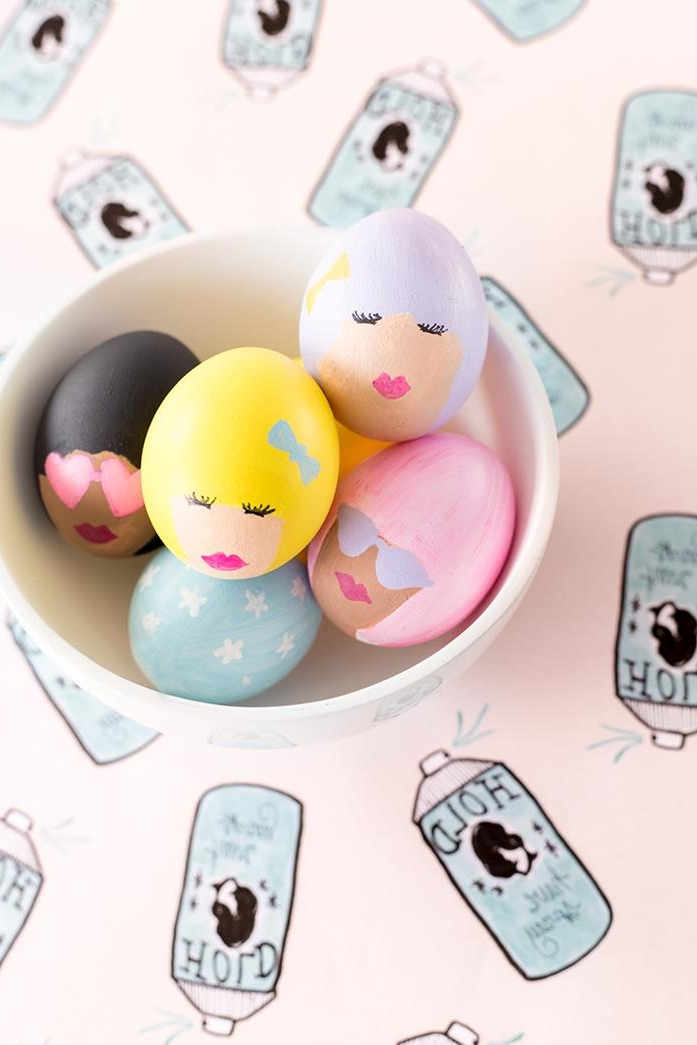 funny women's heads, with pink or yellow, grey or black hair, some with sunglasses, painted on eggs, placed in a white bowl, how to dye easter eggs