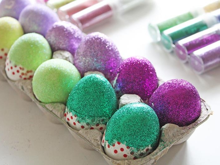 cardboard egg box, with several glitter-covered eggs inside, coloring easter eggs in light and dark purple and green, with washi tape across the middle