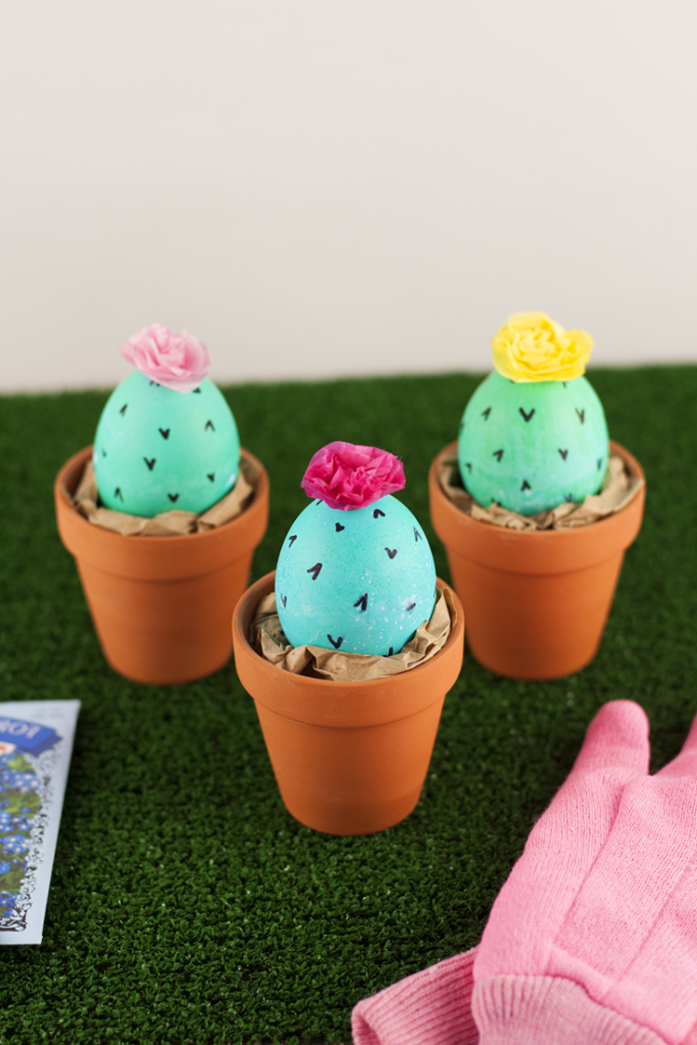 easter egg designs, three eggs painted green, and made to look like cacti, with black thorns drawn in marker, and faux flowers on top, placed in orange ceramic pots