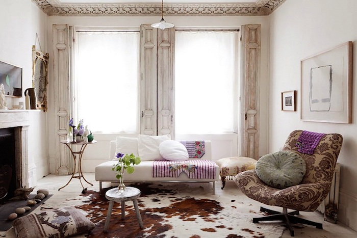 modern shabby chic sofa with striped throw, and white cushions, armchair in grey patterned damask, ox skin rug