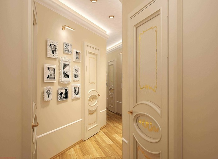 pale cream walls and doors, with plaster details, and golden decorations, hallway decor, light wooden floor, several white frames on wall