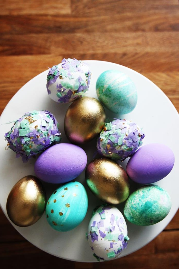dying easter eggs, round white dish, containing eggs dyed in purple, turquoise and shiny golden color, some have patterns, while others are decorated with colorful broken egg shells