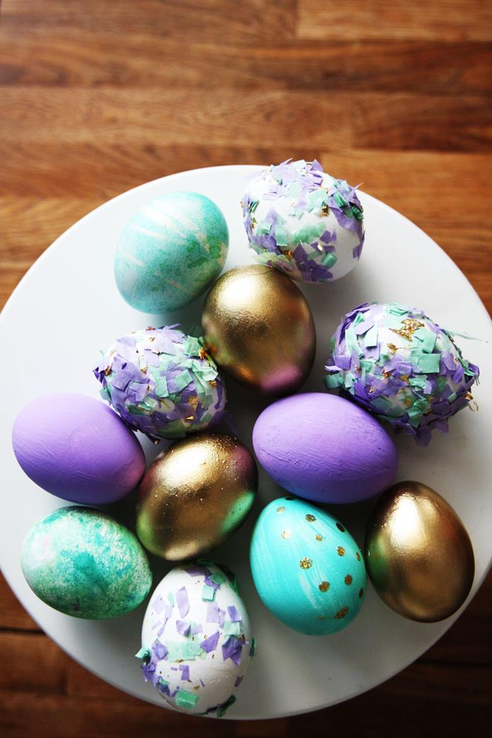 dying easter eggs, eight eggs colored in purple, teal and gold, and four white eggs, decorated with colorful broken egg shells, on a white plate