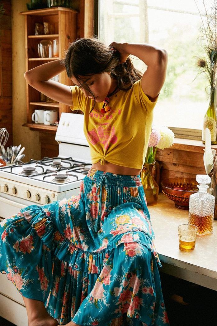 teal tiered maxi skirt, with pink and yellow floral pattern, combined with yellow and pink shirt, bohemian style clothing, on rebellious brunette woman