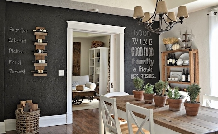 blackboard wall decorated with white chalk writing, large wooden table, partially painted white, with matching white chairs, shabby sheek chandelier and decorations