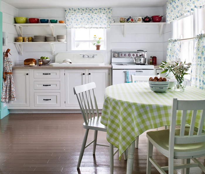 shabby chic decorating, round table with light green and white chequered tablecloth, two mismatched white chairs, brown wooden floor, white kitchen cupboards, and a vintage stove