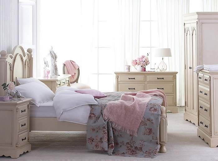 cream-colored wooden cupboards, wardrobe and bed, shabby chic decorating, white bedding with blue floral cover, and pink fluffy throw
