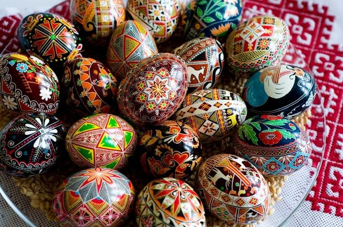 pile of professionally painted easter eggs, various colors and drawings, musician and flowers, animals and birds, european folklore style