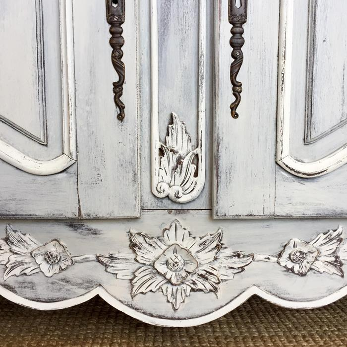 close up of an engraved wooden detail, on antique cupboard, unevenly painted in off-white color, ornamental metal handles