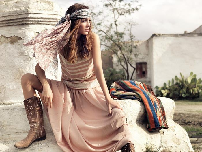 pale pastel pink maxi dress, with white lace details, worn with studded brown cowboy boots, and a large two-tone boho chic headscarf