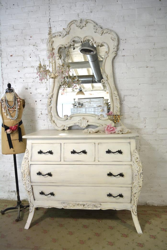 faded floral carpet, under a cream-colored dresser, with ornamental mirror, and black wrought-iron handles, near dressmaker's dummy
