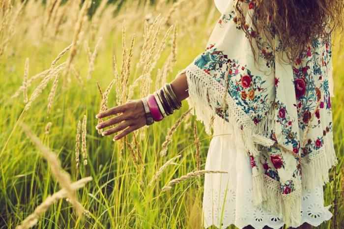 poncho in cream, with multicolored floral pattern and tassels, worn with lots of assorted bangles, and a white broderie anglaise mini skirt, by woman in field