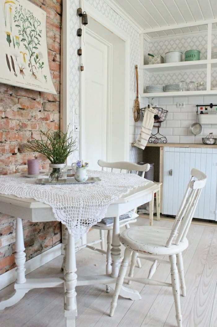 rough brick wall, inside a industrial shabby chic kitchen, white antique table with peeling paint, and matching chairs, various vintage kitchen furniture pieces