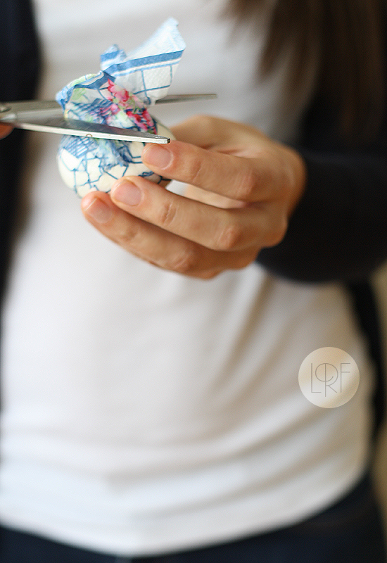 egg wrapped in a paper napkin, woman using scissors, to cut excess napkin, easter egg decorating