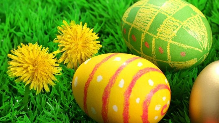 bright green egg, decorated with yellow and red crayon scribbles, near yellow egg, with red and white scribbles, forming a pattern, how to dye easter eggs, green grass and two yellow dandelions