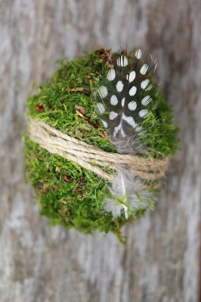 moss covered egg, in bright green, coloring easter eggs, a small dark grey feather, with white spots, is tied to the egg with string