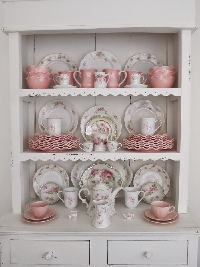 plates and cups in pastel pink, and in white with floral motifs, with matching jugs and teapots, country chic décor, white shabby wooden cupboard