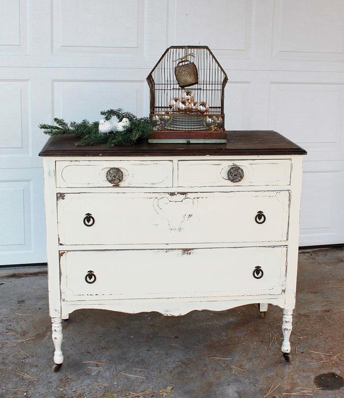 birdcage with vintage look, containing cristmas baubles, country chic décor, placed near a pine branch, on an off-white distressed cupboard, with brown top