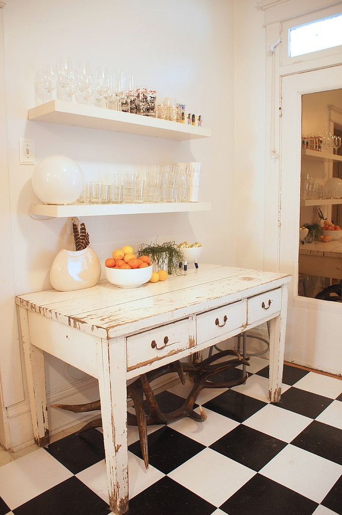 shelves made of wood and painted white, over an antique shabby chic kitchen table, with peeling white paint, black and white tiled floor, glasses and decorations