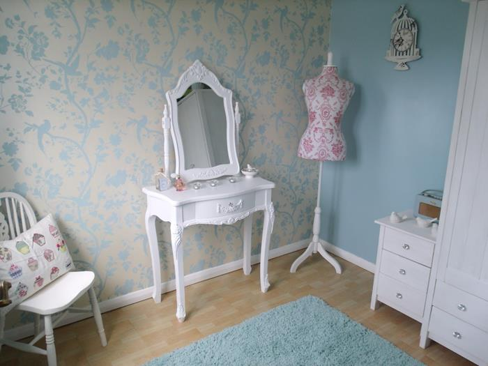 dressmaker's dummy in white and pink, near an ornamental, french antique dresser, shabby chic decorating, cream and pale blue wallpaper, white wardrobe and cupboard