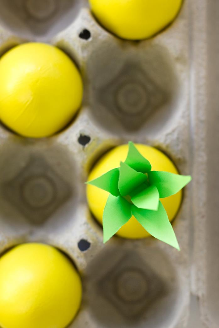 close up of four eggs inside a cardboard box, all painted in yellow, one of them has several paper leaves stuck to its top, making it look like a pineapple, dying easter eggs