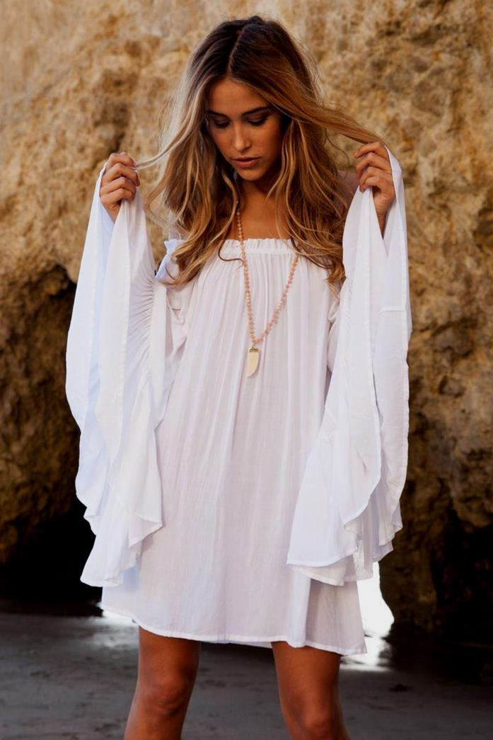 bell-sleeves on white mini dress, bohemian style clothing, worn with delicate gold pendant, by brunette woman with blond balayage