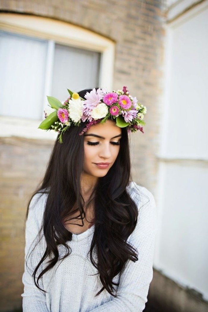 long dark brown, partially curled hair, brunette hairstyles, on a woman in pale grey sweater, wearing large flower crown, with pink white and yellow blossoms