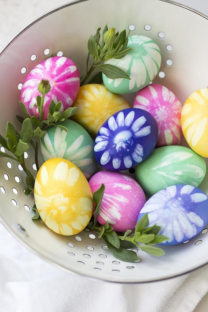 violet and pink, yellow and green dyed eggs, with white flower prints, placed in a white dish with holes, containing green plant leaves