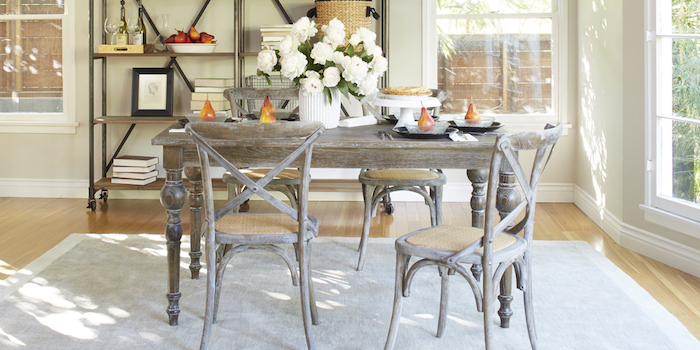 grey-brown antique-looking dining table, with four matching chairs, grey rug and wooden laminate floor, shabby sheek iron shelves, with various items