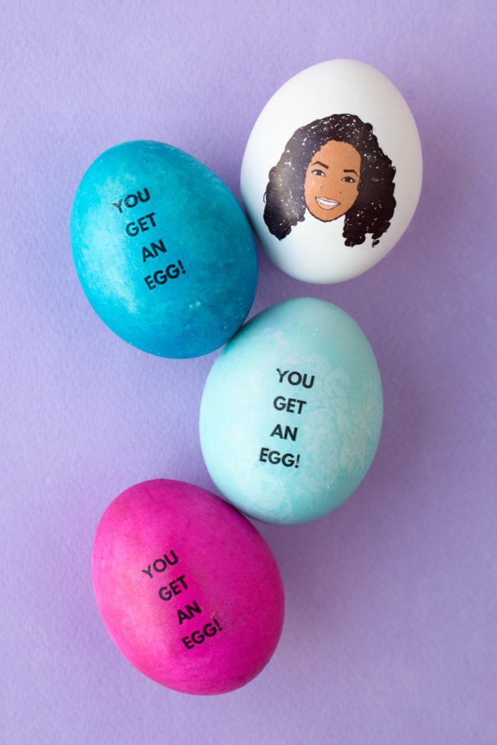 close up of an easter egg with a cartoon drawing of oprah winfrey, placed next two blue eggs, and one pink egg, all bearing the words you get an egg