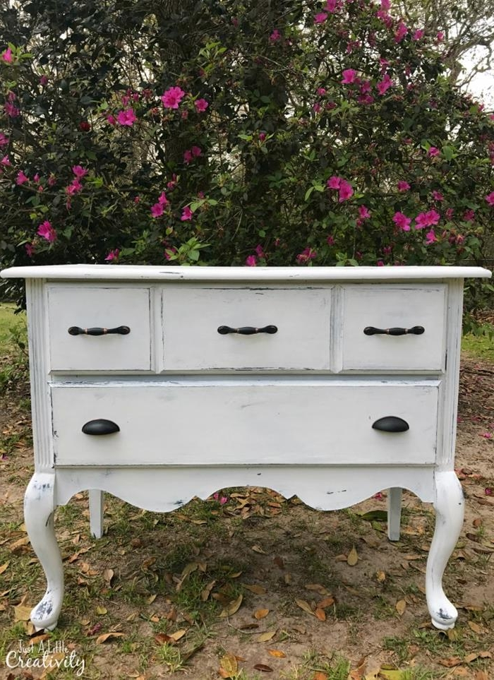 off-white decorative chest of drawers, with black handles, in french antique style, country cottage furniture, placed outside near a blossoming tree