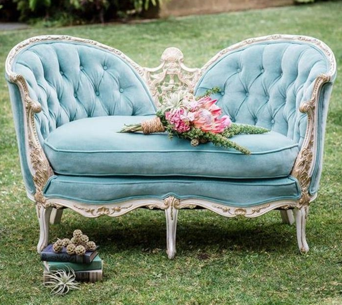 rustic flower bouquet, placed on french sofa in turquoise, with ornamental engraved cream details, placed on a lawn, near books and dried plants