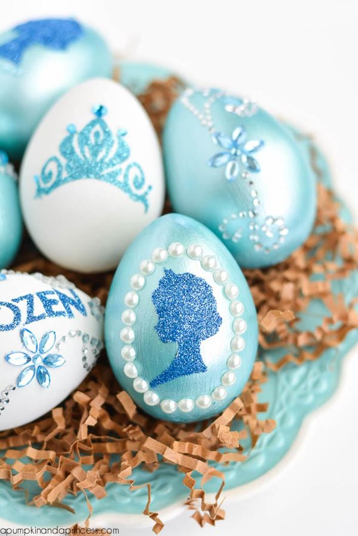 teal easter eggs, decorated with gem and pearl stickers, and blue glitter shapes, inspired by disney's frozen