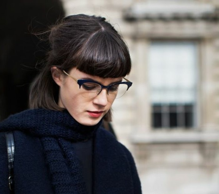 partially tied back hair, with cropped bangs, brunette hairstyles, worn by girl dressed in dark blue, with glasses and chunky knit scarf