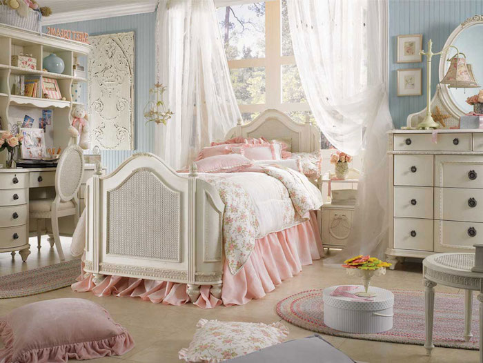 bedroom with pale blue walls, white antique furniture, and matching bed, covered with pale pink and floral bedding, shabby chic decorating, various cushions strewn about