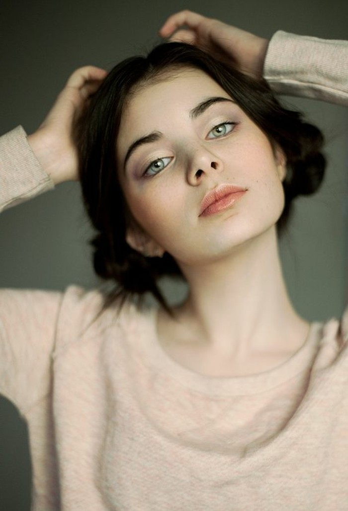 girl with light green eyes, hair parted in the middle, and braided into two side buns, dark brown hair colors, wearing pale pink lipstick, and soft pale pink sweater