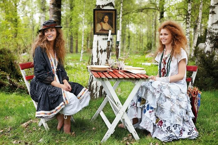 smiling women with voluminous curly hair, sitting on fold-up chairs, near a fold-up table in the woods, wearing bohemian style maxi dresses
