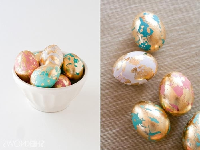 dyed eggs in pink and teal, partially covered in gold leaf, easter egg decorating, placed on beige mat, and inside a white ceramic bowl