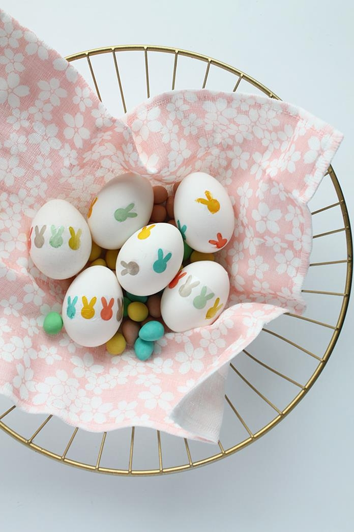 easter egg ideas, pale pink napkin, with white floral pattern, inside a golden basket, containing six white eggs, decorated with multicolored hand-drawn bunny heads, and many small, egg-shaped sweets