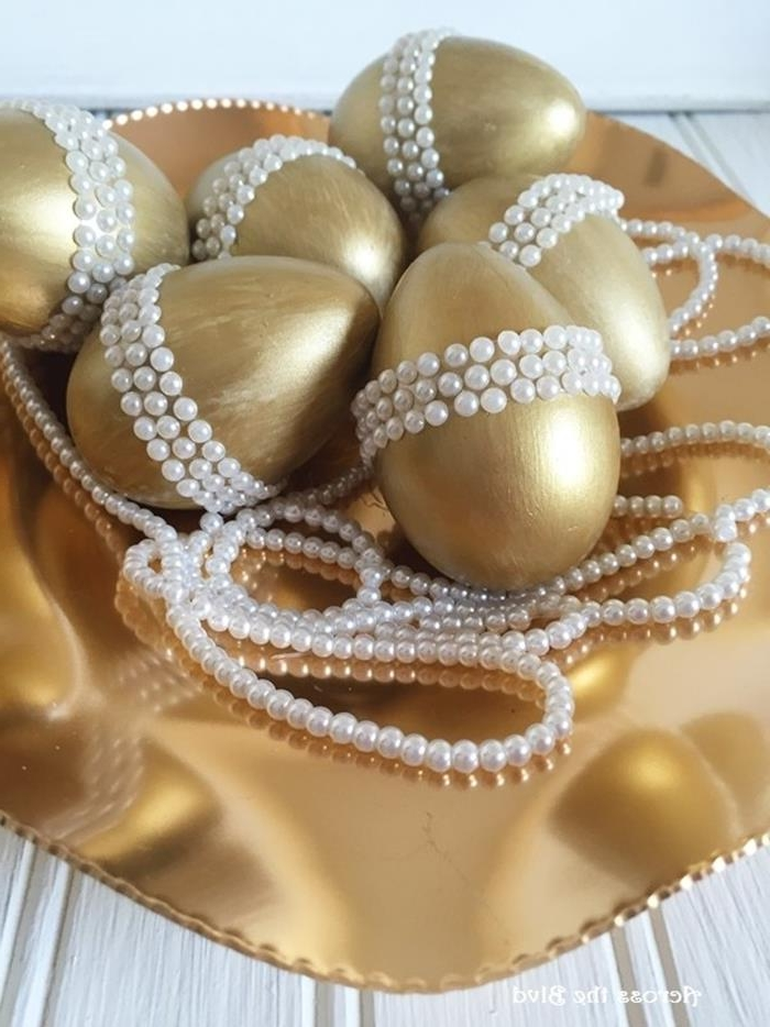 gold-colored metallic dish, containing six eggs painted in gold, and decorated with three rows of white pearl stickers, easter egg decorating, pearl necklace