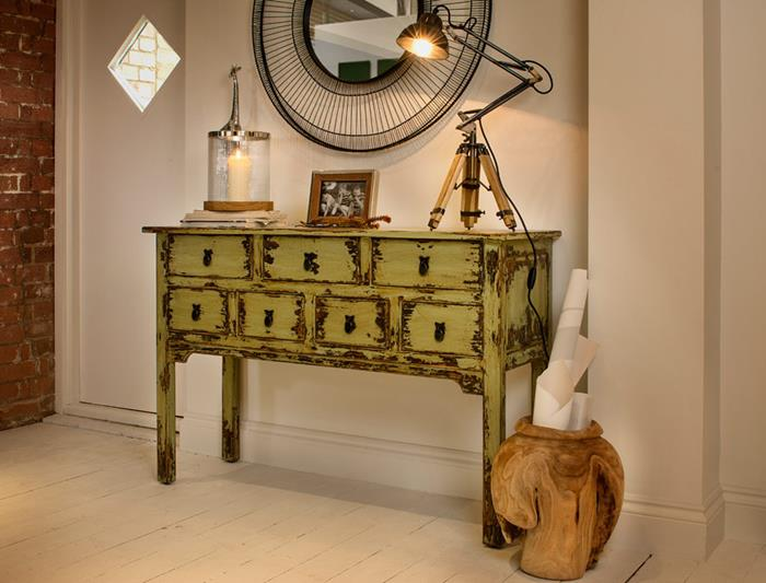 pale acid green chest of drawers, with a lamp, a framed photo and a and a candle, near round mirror, in large ornate black frame, country chic décor