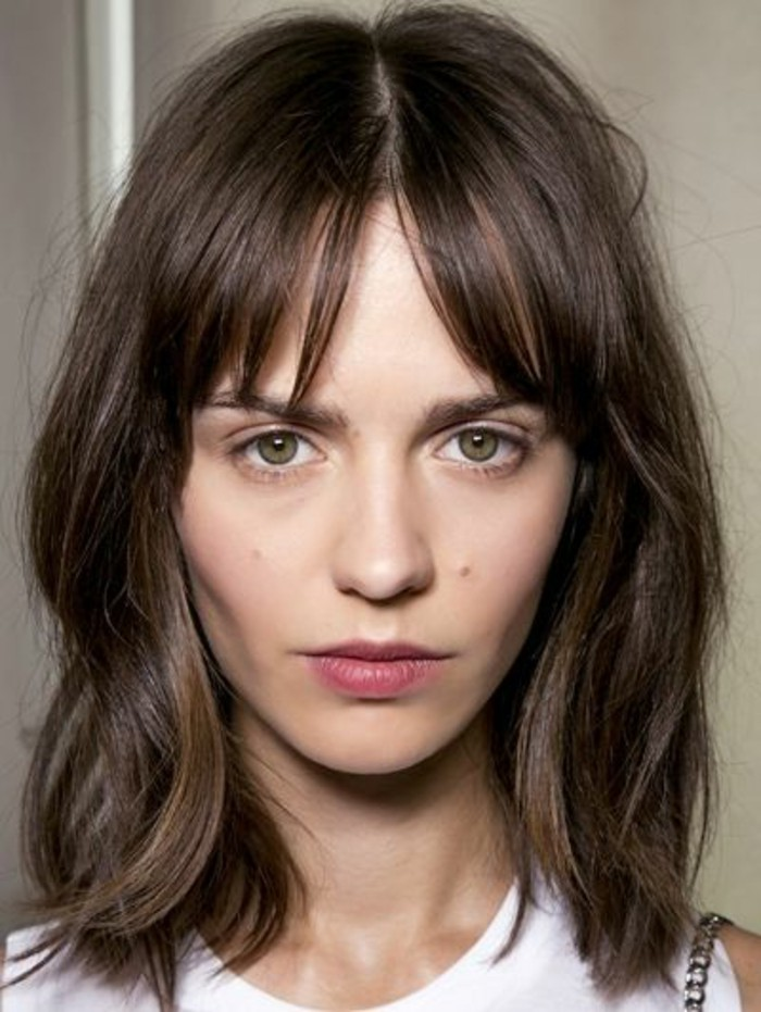 shoulder-length wavy hair, with bangs parted in the middle, brunette hair colors, green-eyed woman, with white sleeveless top, and pale pink lipstick