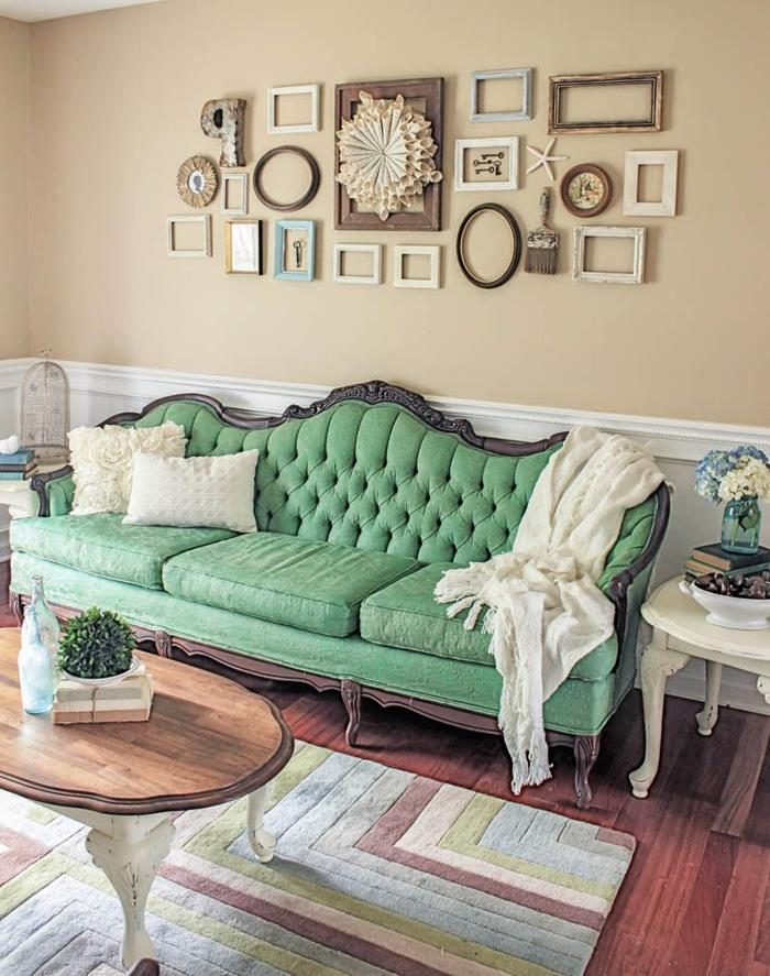 antique green french sofa, with wooden legs and details, two white cushions and a white throw, vintage wooden coffee table, with legs painted white, lots of empty frames on the wall