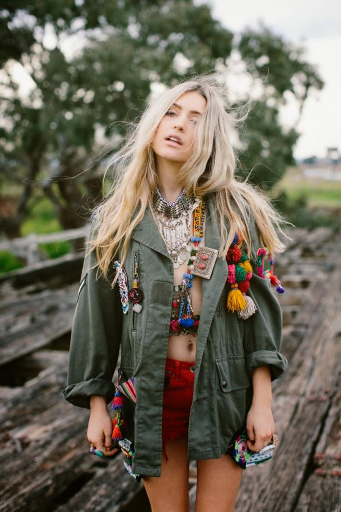 military jacket in green, decorated with boho style aplique details, and colorful pom poms, worn by blonde woman, with long hair, with red shorts, and lots of jewelry