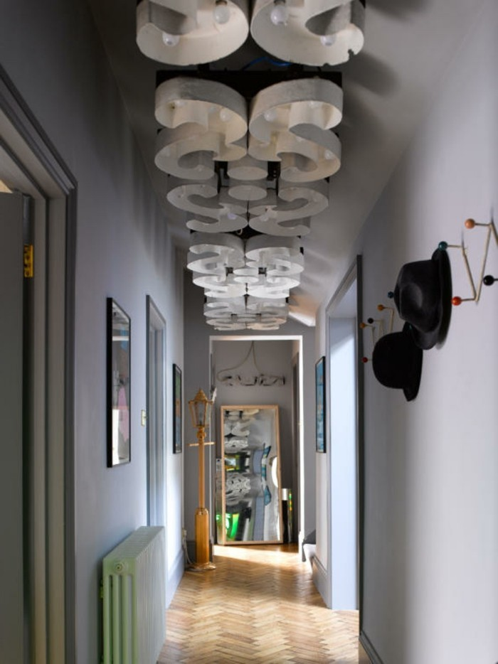 ornate ceiling lights, narrow corridor with pale grey walls, large mirror in wooden frame, hallway decor, laminate floor and coat rack, with two black hats
