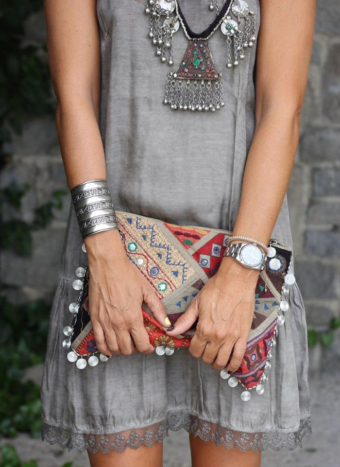 chunky silver tribal necklace with stones, silver bangle and wrist watch, and a multicolored embroidered clutch, with oriental pattern and beads, held by slim woman in grey mini dress, with lace trim, boho style