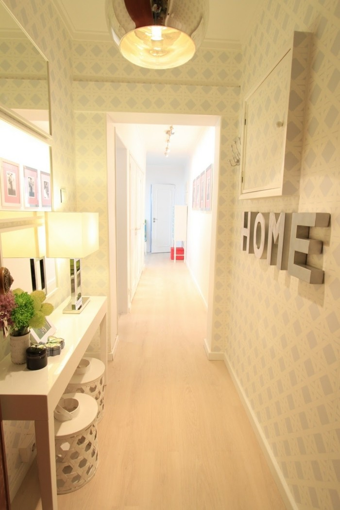 hallway furniture ideas, hall with pale patterned wallpaper, narrow white table, mirror and various decorations
